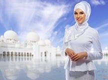 Moslimvrouw op witte moskeeachtergrond stock fotografie