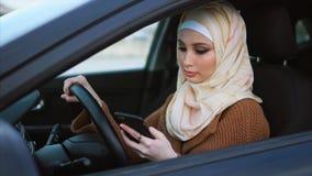 Moslimvrouw tegenwoordig De onderneemster drijft een auto en het babbelen stock video