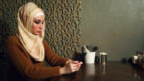 Moslimvrouw tegenwoordig Vrouw die celtelefoon met behulp van, die met iemand texting stock footage