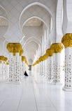 Moslimvrouw in zwarte kledingszitting in een afstand dichtbij witte pijlers Stock Foto's