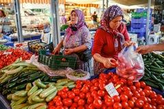 Moslimvrouwen die de groenten in de markt verkopen Kemer, Turkije Royalty-vrije Stock Afbeelding