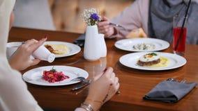 Moslimvrouwen die in een restaurant zitten die salade eten en het zouten stock videobeelden