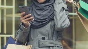 Moslimvrouwen dragende aankopen, die app op telefoon gebruiken aan vraagtaxi na het winkelen stock video
