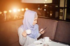 Moslimvrouwenoverseinen op een mobiele telefoon in koffie Stock Foto's