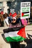 Moslimvrouwenprotesteerder met aanplakbiljet in Gaza: Houd de Slachtingsverzameling in Whitehall, Londen, het UK tegen stock afbeelding