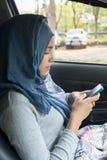Moslimvrouwenzitting met smartphone stock afbeeldingen