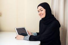 Moslimvrouwenzitting thuis met tabletcomputer, die oortelefoons dragen Rust thuis, voorbereidingen treffend om op een film te let stock fotografie