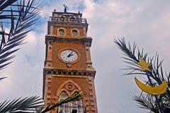 Mosquée avec une horloge sur un fond des feuilles des palmiers et du ciel bleu avec des nuages dans la ville de Haïfa en Israël Photo libre de droits