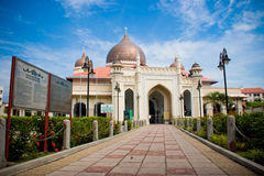 Mosque architecture. Impressive mosque architecture with front bricks walk way blue sky white clouds Royalty Free Stock Image