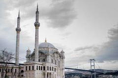 A mosque and bridge in background on cloudy day. stock photos