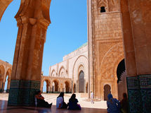Mosque in Casablanca. People resting in the shade of a tall portico on a hot day  in Casablanca Hassan II mosque, Morocco Stock Photos