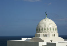 Mosque dome. White marble mosque dome on the coast of Gibraltar, under a blue sky with the sea in the background Stock Photo