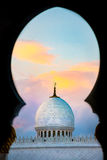 Mosque dome through arch. Mosque dome at sunset with colourful clouds through arch Stock Images