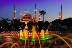 Mosque and fountain. Blue mosque and fountain in Istanbul illuminated at evening, Turkey. Inscription on a mosque is translated as On him is a soul of everyone royalty free stock photo