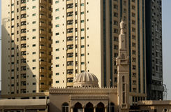 Mosque in front of tall high-risings Stock Photos