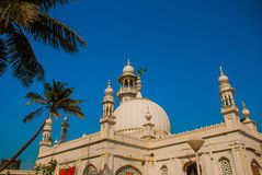 Mosque Haji Ali. Mumbai, India. Fragment of a building on blue sky background. Palma. Mosque in middle of the sea in Mumbai. Haji Ali Royalty Free Stock Photography