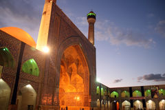 Mosque illuminated at dusk. Exterior of historic mosque illuminated at dusk with blue sky and cloudscape background royalty free stock photography