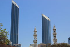 Mosque minaretes contrasted with modern skyscrapers. Two minarets of a mosque and two modern skyscrapers against the backdrop of a clear blue sky contrasting old Royalty Free Stock Photography