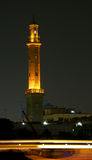 Mosque at Night. A tall minaret of a middle eastern mosque stands along side a waterway at night Stock Photos