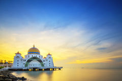 Mosque by the sea during sunrise with colorful sky Stock Photo