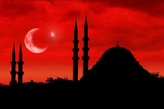 Mosque silhouette as the turkish flag during sunset. Mosque silhouette during red sunset with Turkish flag, moon and star stock images
