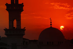 Mosque in sunset. A traditional mosque with dome and part of the minaret etched against a sunset. The sun is partially obscured by a cloud stock image