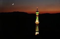 Mosque in Syrian nightscape. A Syrian nightscape during sunset with a brightly lit mosque and the moon Stock Photo