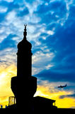 Mosque tower silhouette over the blue sky on dusk and a plain landing in background. Plain landing on background and mosque tower Stock Images