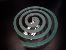 Mosquito coil on coil holder. New mosquito coil on coil holder with the darkness Royalty Free Stock Images