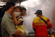 MOSQUITO EXTERMINATION. A small girl closes her nose when a city sanitary official exterminate mosquitos, at Solo, Java, Indonesia Royalty Free Stock Photos