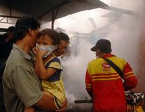 MOSQUITO EXTERMINATION. A small girl closes her nose when a city sanitary official exterminate mosquitos, at Solo, Java, Indonesia Stock Image