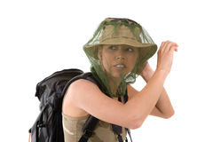 Mosquito fright. Pretty blond girl hiding her face behind a mosquito net that goes over her hat Royalty Free Stock Photography