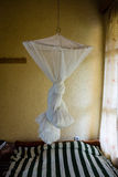 Mosquito Net, Rwanda. Mosquito net, tied up and ready for use, above a stripy bedspread in a basic hotel room, Ruhengeri, Northern Province, Rwanda Royalty Free Stock Images