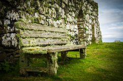 Moss coverd bench at Trumpan Church on Isle of Skye in Scotland. A moss coverd old wooden bench at Trumpan Church on Isle of Skye in Scotland royalty free stock photo
