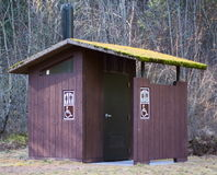 Moss covered Outhouse in Dense Forest Royalty Free Stock Photos