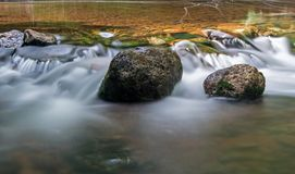 Short Water Drop Over Rocks On The Boyne River. A moss covered rock sits solid in the fast moving waters of the Boyne River, just upstream from Hoggs Falls. The royalty free stock images