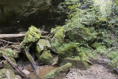 Moss covered rocks and small stream. Large moss covered boulders piled up in a rugged hollow in West Virginia with a small creek flowing from the jumble of rocks royalty free stock images