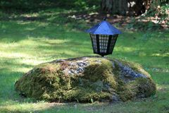 Moss-covered stone on the green lawn. Behind the stone hid the old lantern.nnn stock image