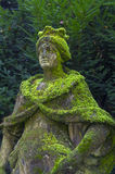Moss-covered stone statue of the Queen in the park. Stock Image