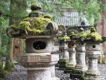 Moss Covered Stone Statues i en kiselstenträdgård Arkivbilder