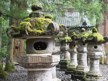 Moss Covered Stone Statues in a pebble garden.  Stock Images