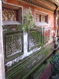 Moss Covered Wall. Bali - May 2014  A moss covered walll in the Puri Saren Royal Palace in Ubud, Bali. The wall has a number of craved panels showing intricate Royalty Free Stock Photography