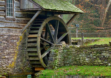 Moss covered water wheel and stone retaining wall of a historic Royalty Free Stock Image