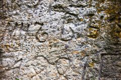 Moss-grown surface of the old stone cross. With engraved Old Church Slavonic inscriptions. Kyiv, Ukraine. Close up Stock Images