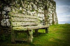 Mossacoverdbänk på den Trumpan kyrkan på ön av Skye i Skottland Royaltyfri Foto