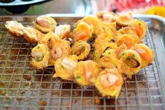 ` mosselen, garnalen, pijlinktvis/octopus ` in Takoyaki-ballen op metaalnet Stock Fotografie