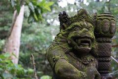 Mossig staty i Bali Indonesien med djungeln och palmträd i baksidan Royaltyfri Fotografi