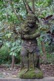 Mossig staty i Bali Indonesien med djungeln och palmträd i baksidan Royaltyfri Foto