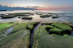 Mossigt vagga vid yhehavet med solnedgång Royaltyfri Fotografi