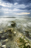 Mossy rocks along the coastline with dramatic dark clouds. Soft focus and blurred image of mossy rocks along the coastline with dramatic dark clouds Stock Photo